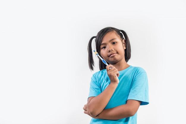 Klein meisje haar tanden poetsen in studio opname Gratis Foto