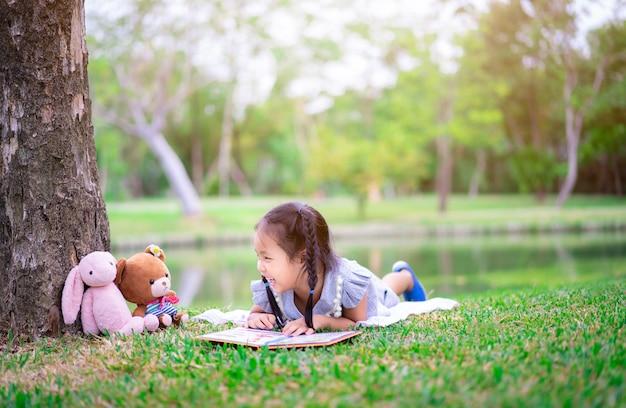Klein meisje het lezen van een boek liggend met een pop Premium Foto