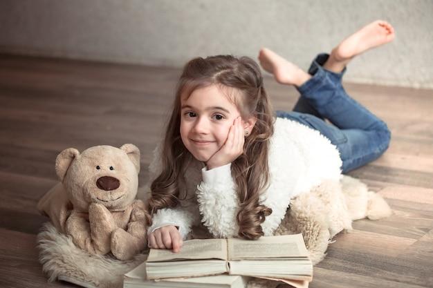 Klein meisje het lezen van een boek met een teddybeer op de vloer, concept van ontspanning en vriendschap Gratis Foto
