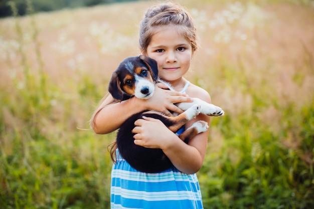 Klein meisje houdt een puppy op haar armen Gratis Foto