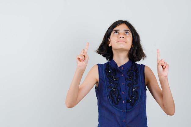 Klein meisje in blauwe blouse die vingers benadrukt en dankbaar kijkt Gratis Foto