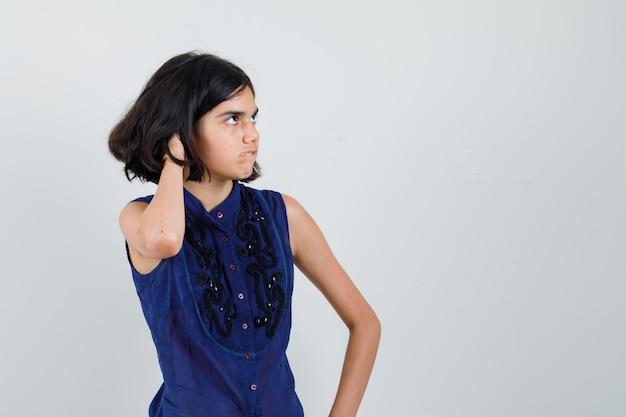 Klein meisje in blauwe blouse hoofd krabben, lip bijten en op zoek angstig Gratis Foto