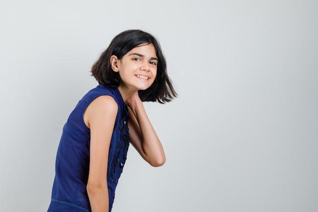 Klein meisje in blauwe blouse poseren met hand op nek en optimistisch op zoek. Gratis Foto