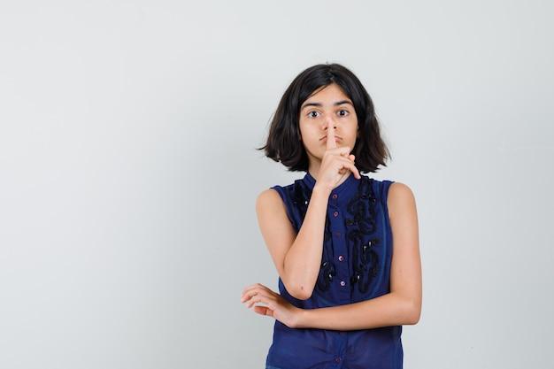 Klein meisje in blauwe blouse stilte gebaar tonen en voorzichtig kijken Gratis Foto