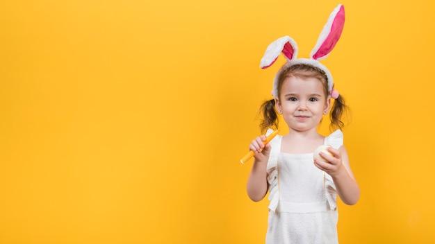 Klein meisje in bunny oren met ei en viltstift Gratis Foto