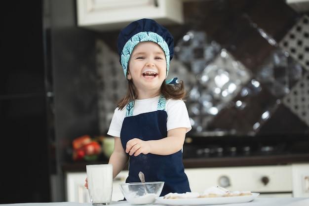 Klein meisje in de keuken in een schort en een koksmuts drinkt melk Premium Foto