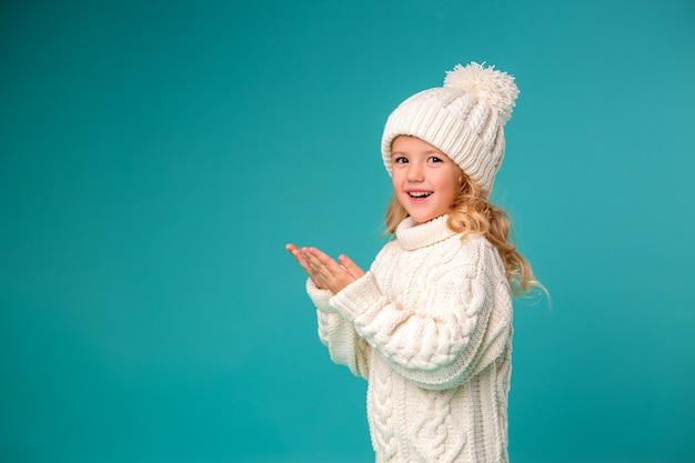 Klein meisje in de winter gebreide muts en trui Premium Foto