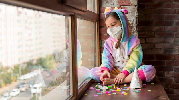 Klein meisje in dinosauruskostuum thuis met gezichtsmasker Premium Foto