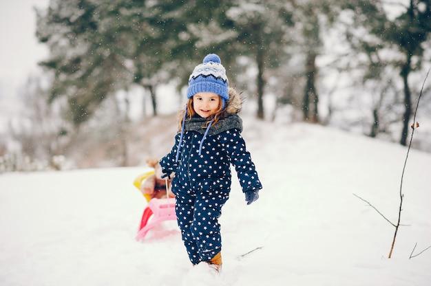Klein meisje in een blauwe hoed die in een de winterbos speelt Gratis Foto