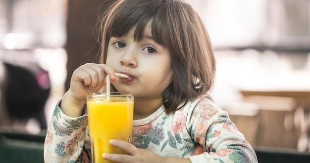 Klein meisje in een café drinken sap Gratis Foto