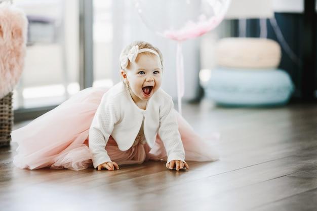 Klein meisje in een charmante roze jurk met open mond kruipt op de vloer Gratis Foto