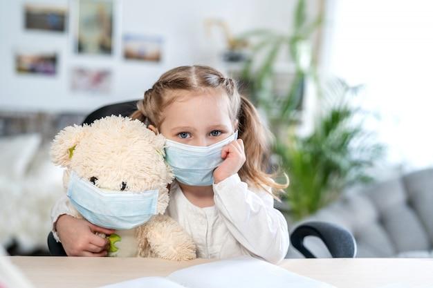 Klein meisje in een masker, knuffelen een teddybeer, op zoek verdrietig, concept van e-learning Premium Foto