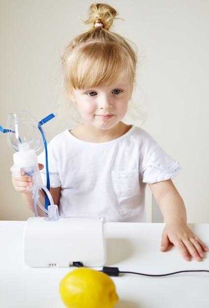 Klein meisje in een masker voor inhalaties, waardoor inhalatie met vernevelaar thuis inhalator op de tafel, binnen, ziek kind Premium Foto