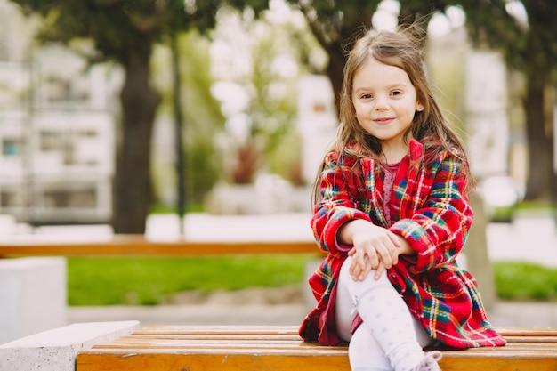 Klein meisje in een park zittend op een bankje Gratis Foto