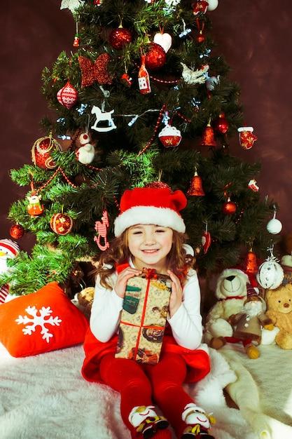 Klein meisje in een rode jurk zit met een huidige vak voor een kerstboom Gratis Foto