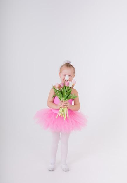 Klein meisje in een roze jurk met een tutu rok staat met een boeket tulpen op een witte muur Premium Foto
