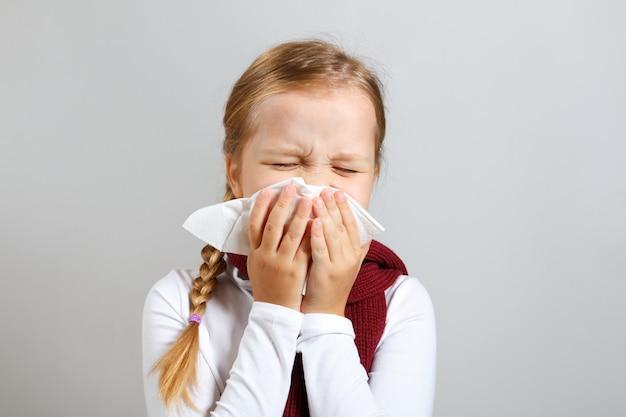 Klein meisje in een warme sjaal blaast haar neus. Premium Foto