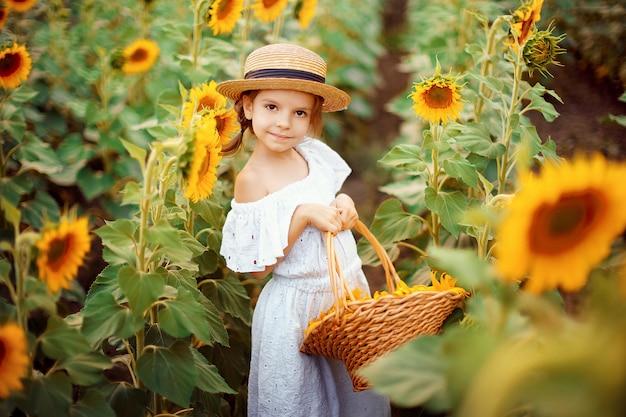Klein meisje in een witte jurk, een strooien hoed met een mand vol zonnebloemen glimlachen naar de camera in een veld met zonnebloemen Premium Foto