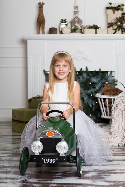 Klein meisje in een witte jurk rijdt op een vintage kinderauto in kerstversiering Premium Foto