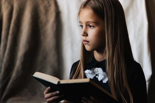 Klein meisje in een zwarte jurk houdt een groen boek en leest het. Premium Foto