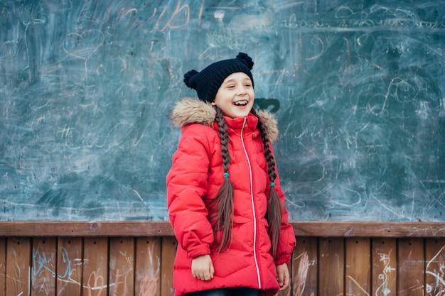 Klein meisje in herfst park staat op het schoolbestuur. Gratis Foto