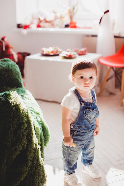 Klein meisje in jeans springers staat in de kamer Gratis Foto