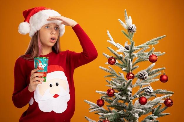 Klein meisje in kerstmissweater en kerstmuts met kleurrijke papieren beker op zoek ver weg naast een kerstboom op oranje achtergrond Gratis Foto