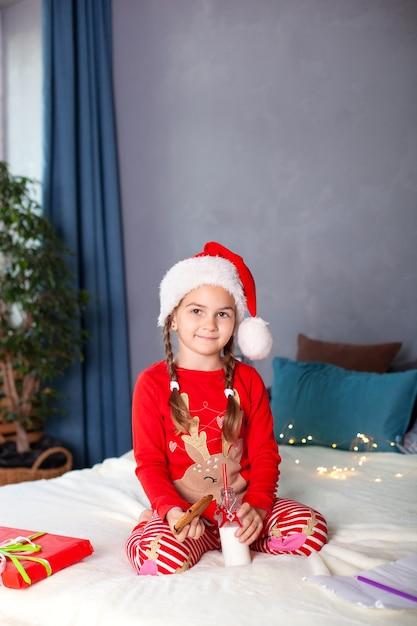 Klein meisje in pyjama's zit met melk en kerstkoekjes Premium Foto