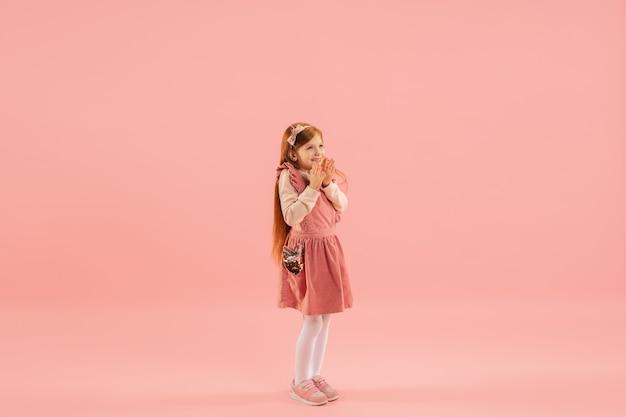 Klein meisje in roze jurk op roze muur Gratis Foto