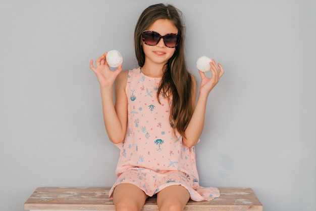 Klein meisje in roze jurk zitten in zonnebril met marshmallows in haar handen tegen grijze muur Premium Foto