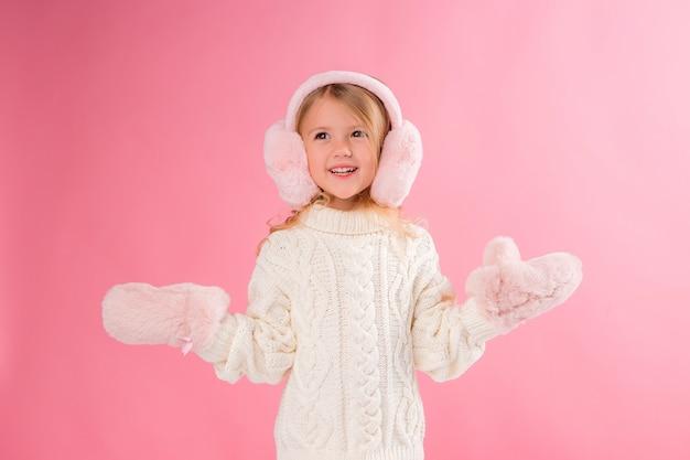 Klein meisje in roze wanten en koptelefoon op een roze muur Premium Foto