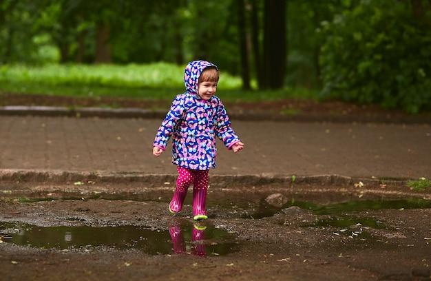 Klein meisje in rubberlaarzen heeft plezier wandelen in de zwembaden na de regen Gratis Foto