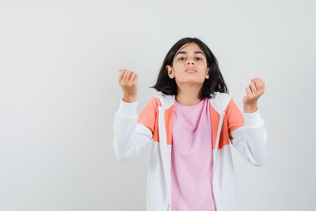 Klein meisje in t-shirt, jasje doet italiaans gebaar en kijkt ontevreden Gratis Foto