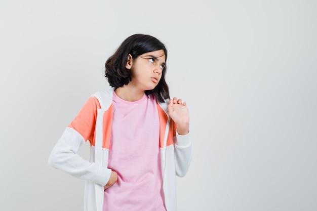 Klein meisje in t-shirt, jasje opzoeken en streng kijken Gratis Foto