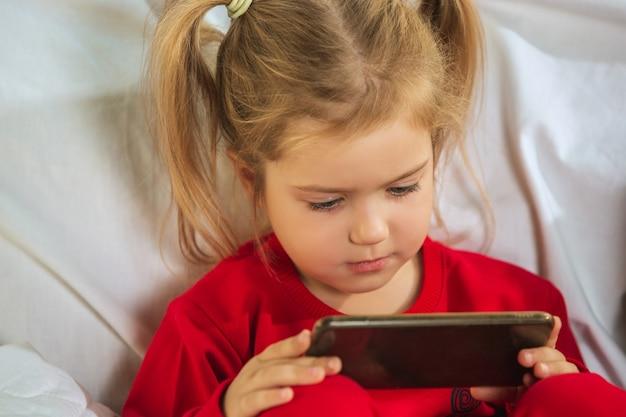 Klein meisje in zachte warme pyjama thuis spelen Gratis Foto