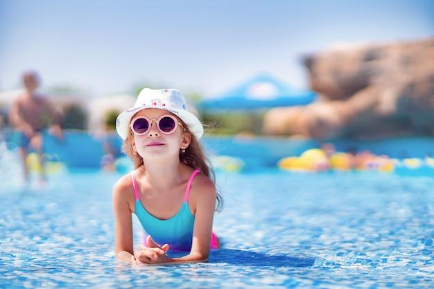 Klein meisje in zonnebril en hoed met eenhoorn in het buitenzwembad van luxe resort op zomervakantie op tropisch strand eiland Premium Foto