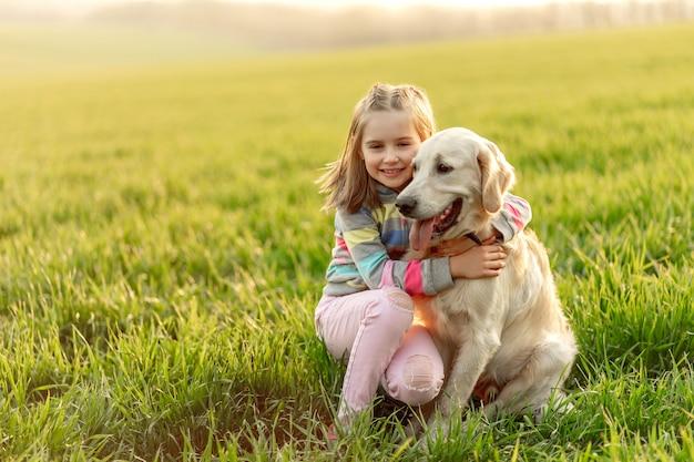 Klein meisje knuffelen mooie hond Premium Foto