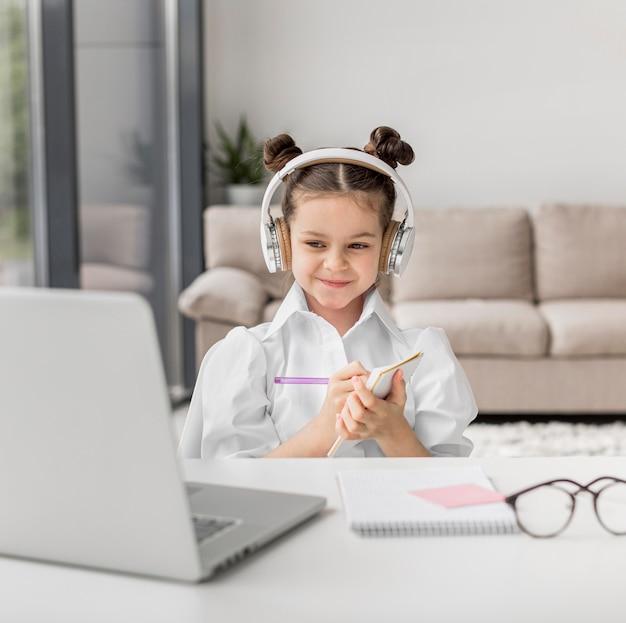 Klein meisje luisteren naar haar leraar via hoofdtelefoon binnenshuis Gratis Foto