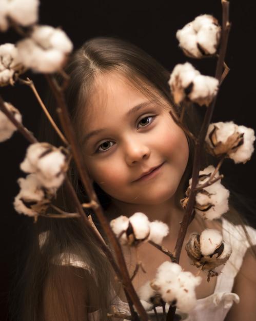 Klein meisje met een boeket van katoen Premium Foto