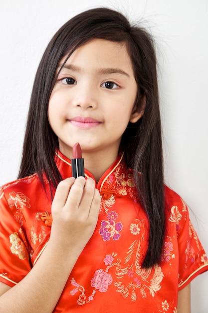Klein meisje met rode lippenstift Premium Foto
