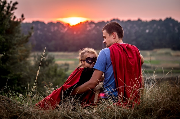 Klein meisje met vader gekleed in super helden, gelukkig liefdevolle familie Gratis Foto