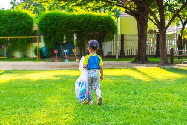 Klein meisje op een speelplaats. kind buiten spelen in de zomer. Premium Foto