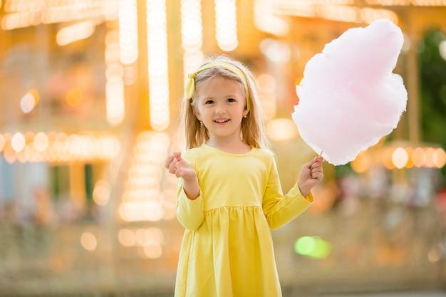 Klein meisje op een wandeling in een pretpark suikerspin eten Premium Foto