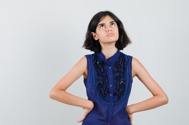 Klein meisje opzoeken in blauwe blouse en nieuwsgierig kijken, Gratis Foto