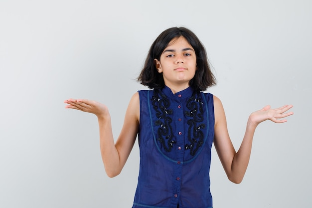 Klein meisje schalen gebaar maken in blauwe blouse Gratis Foto