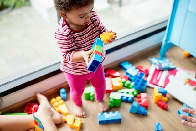 Klein meisje spelen met bouwstenen Gratis Foto