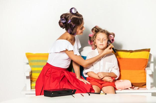 Klein meisje spelen met de make-up van haar moeder Gratis Foto