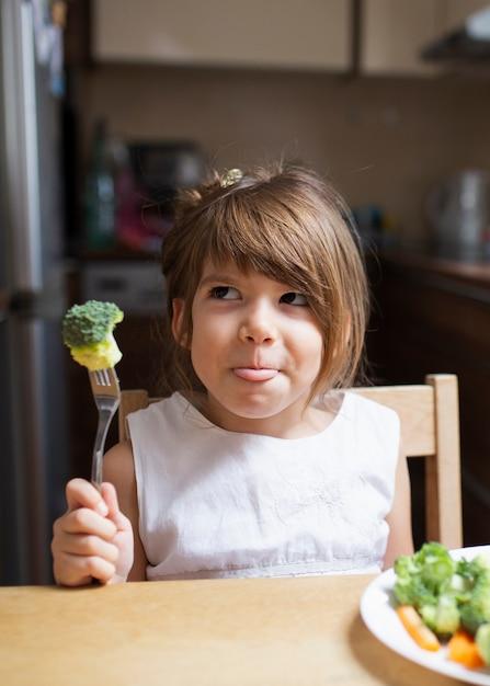 Klein meisje spelen met gezond voedsel Gratis Foto