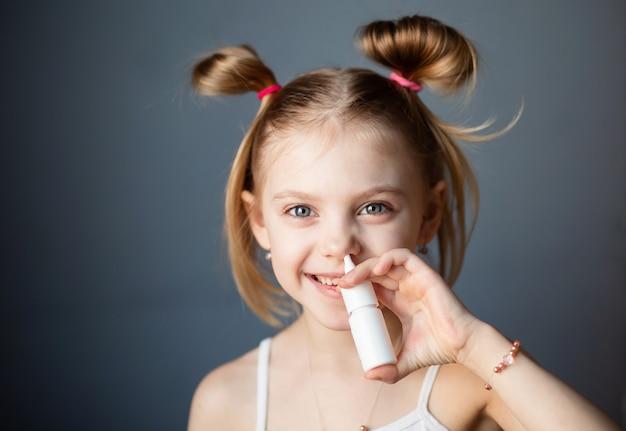 Klein meisje strooit een neusspray Premium Foto