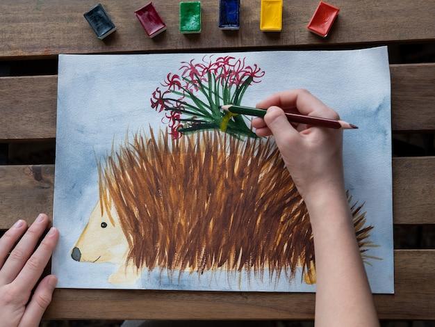 Klein meisje tekent een egel met aquarellen en potloden Premium Foto